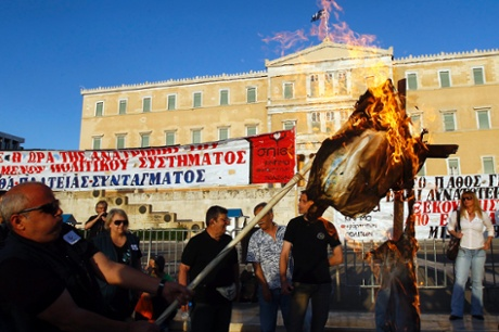 epa03680539 Protesters burn an effigy symbolizing a Greek worker during a protest rally, organized by the umbrella trade union groups General Confederation of Employees of Greece (GSEE) and the civil servants' union federation ADEDY, in front of the Greek Parliament in Athens, Greece, 28 April 2013.