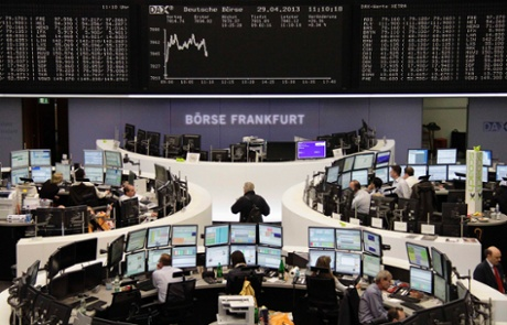 Traders work at their desks in front of the DAX board at the Frankfurt stock exchange April 29, 2013.