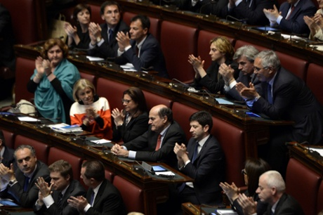 Italian deputies applaud out-going Democratic Party (PD) general secretary Pier Luigi Bersani (C - red tie) as Italy's new Prime Minister Enrico Letta delivers his speech at the Parliament in Rome on April 29, 2013.