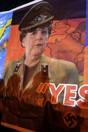 A poster depicting German Chancelor Angela Merkel as a Nazi officer, outside Cyprus presidential palace during a protest last week.