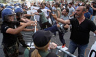 Demonstrators clash with police outside the parliament building in Nicosia