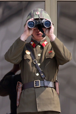 Meanwhile, a North Korean soldier looks through binoculars at the truce village of Panmunjom in the demilitarized zone (DMZ) dividing the two Koreas this morning.