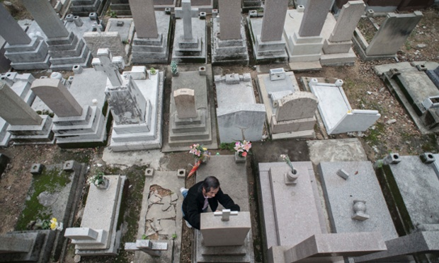 A man kneels to retrace with a black pen the inscription on the tombstone of a loved one at a Catholic cemetery during the Ching Ming festival, or grave-sweeping day, in Hong Kong.
