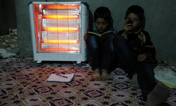 Abdurrahman, aged six, and Osman, 10, keep warm at home in Cizre in Turkey's Sirnak province, near the border with Syria. Photograph: Umit Bektas/Reuters