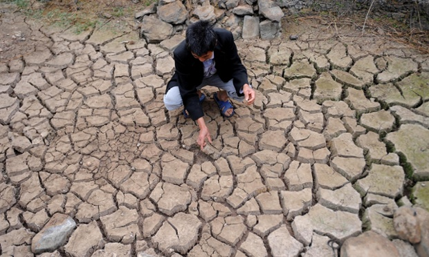 A local man squats in a dried-up field in Hulu village, Chengdu, China. A severe drought has lingered over most areas of Sichuan province since the winter, affecting more than 2.6 million people.