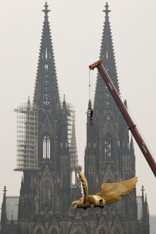 The 'Fluegelauto' by German artist HA Schult is lowered by a crane on to the top of Cologne's historic armoury. The Fluegelauto is, slightly disappointingly, a 1989 Ford Fiesta.