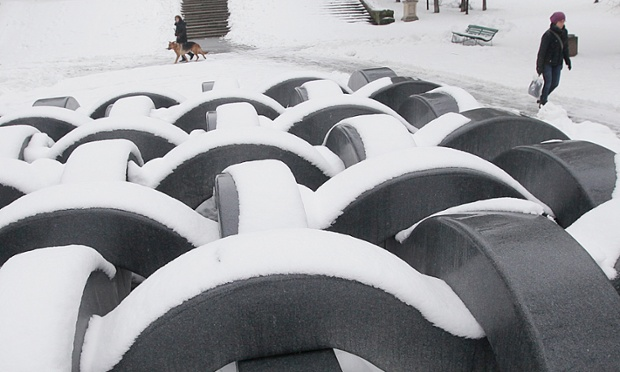 People walk past a sculpture in a park in Warsaw, Poland. Snow continues to fall across the country with temperatures slightly above 0C. It's also very cold in London!