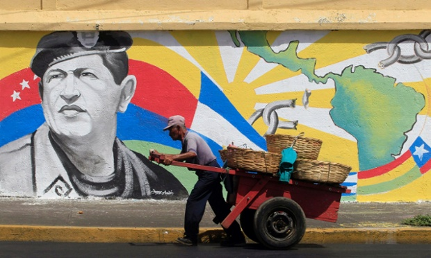 A street vendor in Managua pulls his cart past a mural of Venezuela's late president, Hugo Chávez. Members of Juventud Sandinista (Sandinista Youth) made the mural to mark the first month of his death.