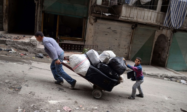 On another continent: young Syrians pull a cart as they leave the Sheikh Maqsud neighbourhood in Aleppo. The UN says more than 70,000 people have been killed in the civil war.