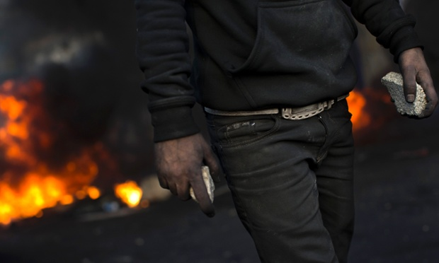 A Palestinian protester holds stones to be used against Israeli forces, during clashes in the West Bank city of Hebron.