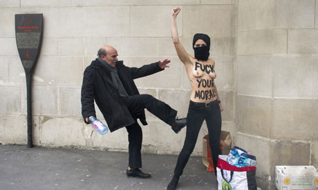 A man kicks a topless Femen activist in Paris