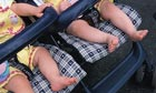 Twin babies bare feet hanging out of a stroller