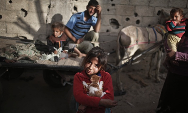 A Palestinian girl holds her cat in front of her family house in Bait Lahiya town, North Gaza Strip. The United Nations Relief and Works Agency (UNRWA) said in a statement it's had to reduce cash payments to the poorest refugee families in the Gaza Strip as a result of budget shortfalls.
