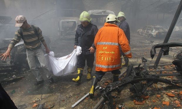 Rescue teams recover bodies from the scene of a car bomb explosion which rocked central Damascus this morning. The blast, which was followed by intense gunfire, occurred near the Syrian central bank causing deaths and injuries, according to Syria's state television.