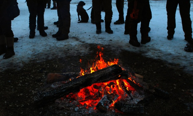 Hunters (and their dog) stand next to a campfire before an event at a U.S. military training area in Hohenfels near Regensburg, Germany. The hunt takes place during the closed season for hunting game at one of Germany's biggest military training grounds.