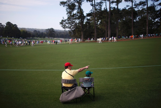 Spectators watch from the first fairway during a practice round in preparation for the 2013 Masters golf tournament at the Augusta National Golf Club in Augusta, Georgia, United States.