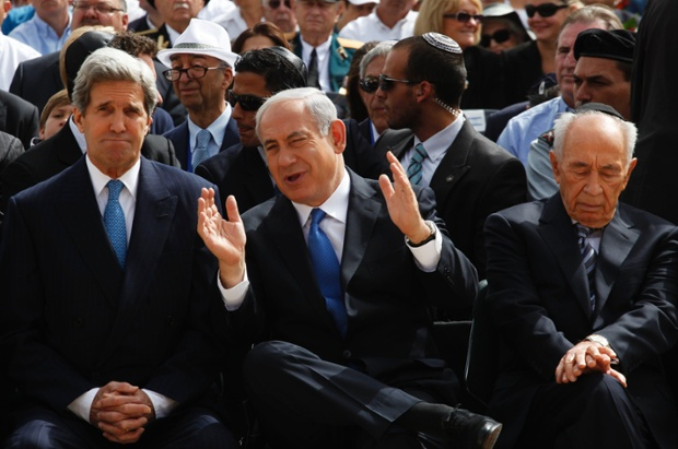 Israeli Prime Minister Benjamin Netanyahu (C) speaks with US Secretary of State John Kerry as President Shimon Peres (R) sits beside them during a ceremony marking Israel's annual day of Holocaust remembrance, at Yad Vashem in Jerusalem. Israel commemorates the six million Jews killed by the Nazis in the Holocaust during World War Two.