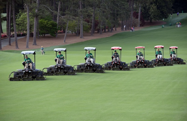 A row of lawn-mowing machines come down the fairway during a practice round at the 77th Masters golf tournament at Augusta National Golf Club in Augusta, Georgia.