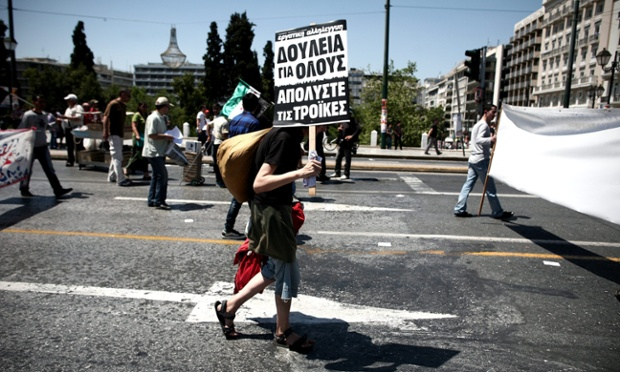 A protestor holds a placard that reads 'Jobs for everyone, fire the troikas'  during a rally marking May Day in central Athens, Greece, 01 May 2013.