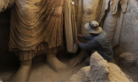 An Afghan archaeologist looks at Buddha statues at Mes Aynak.