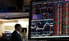 A Bloomberg terminal displays news while traders work on the floor of the New York Stock Exchange