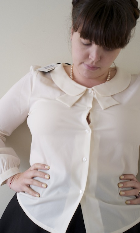 Woman wearing a shirt with buttons gaping open over the bust