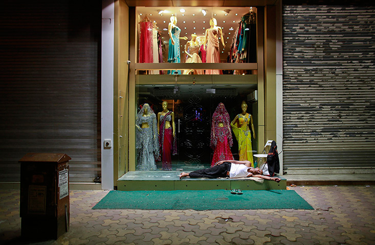 24 hours: A security guard sleeps outside a closed garment shop in Mumbai