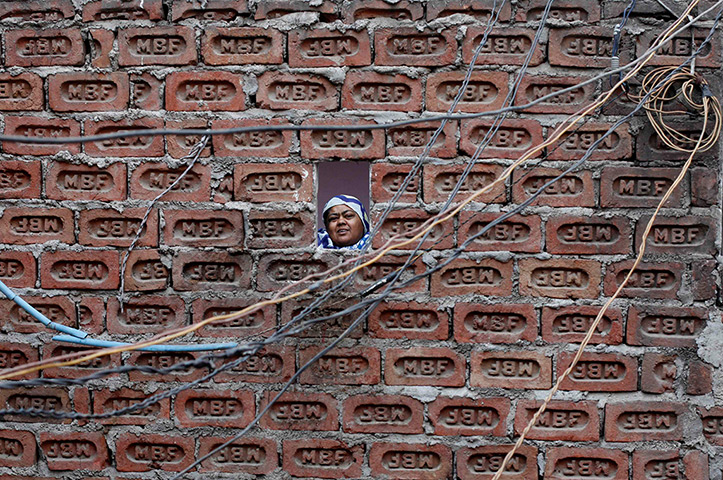 24 hours: Delhi, India: A woman looks from behind a brick wall