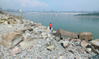 A man fishes near the Three Gorges dam, the world&#39;s most powerful hydroelectric project