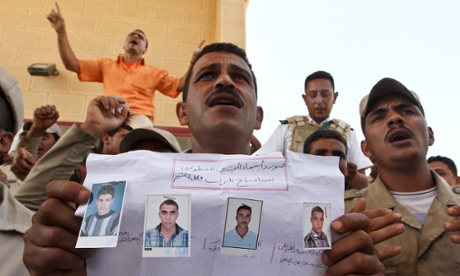 An Egyptian border policeman displays pictures of four of their colleagues who were kidnapped last Thursday, during a protest at the closed Rafah border crossing between Egypt and the Gaza strip, in Rafah, Egypt. Security officials said 17 military and more than 20 police armoured vehicles were deployed in northern Sinai Monday as a response to the kidnapping.