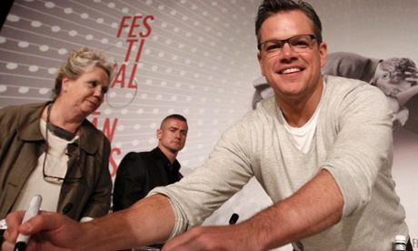 Matt Damon signs autographs as he arrives at a news conference for the Behind the Candelabra