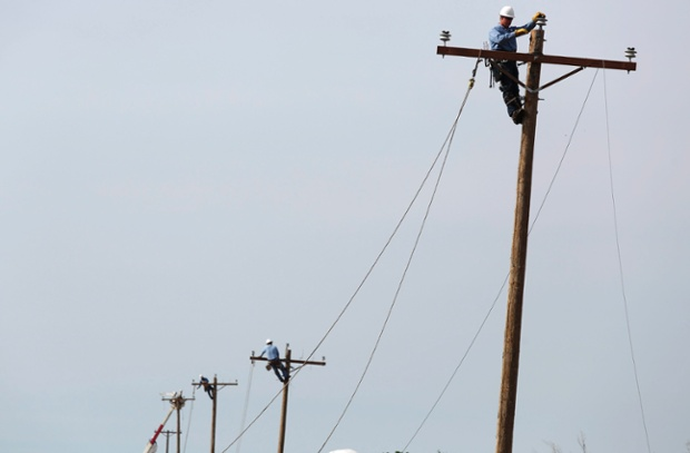 As the clear-up gets under way, utility workers raise cable as they try to restore power to a section of town in Moore, Oklahoma.