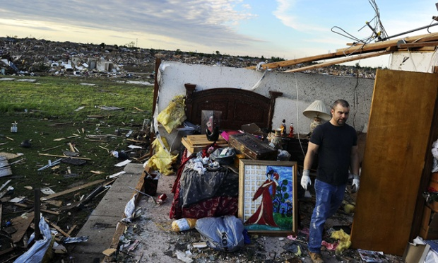 Here a man salvages things from what is left of a bedroom of his tornado devastated home.