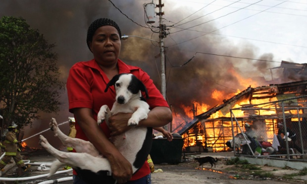 In the El Chorrillo neighborhood in Panama City a woman carries a dog as a fire blazes in the background. More than seventy wooden homes were set on fire by unknown causes, leaving more that one hundred people homeless.
