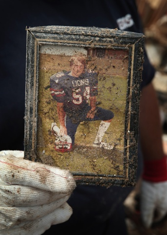 Curtis Cook salvages his high school football photo from the rubble of his family's house after a powerful tornado destroyed his home in Moore, Oklahoma. The same photo was also recovered after his parent's home was destroyed in a tornado in 1999.
