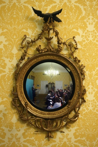 Deputy Prime Minister Nick Clegg is reflected in a mirror while speaking during a press conference at Admiralty House in London.
