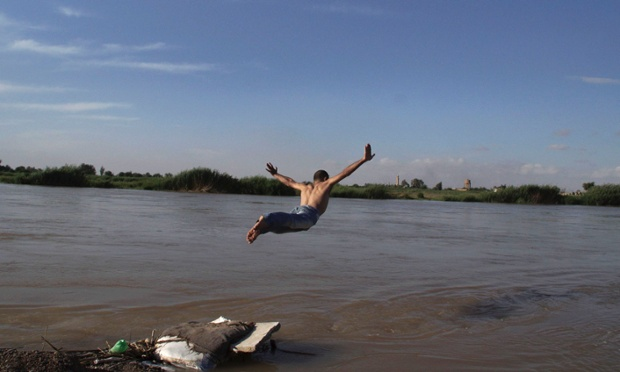 A member of the Free Syrian Army dives in the Euphrates river in Deir al-Zor.