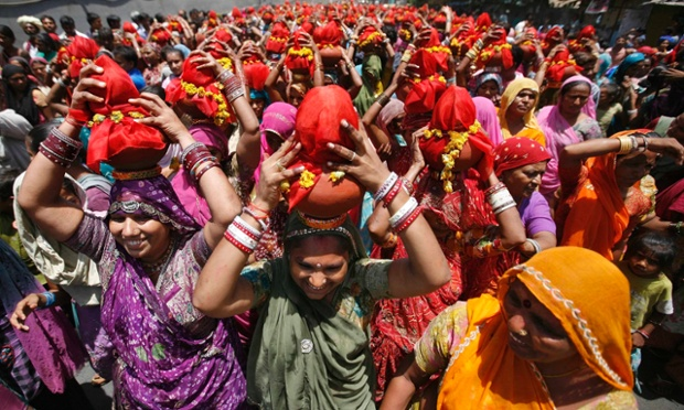 Hindu women carry Kalash, earthen pots containing sacred water with a coconut on top, during a religious procession known locally as Ganga Kalash Yatra in the western Indian city of Ahmedabad.