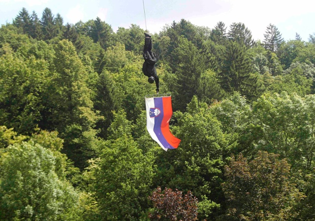 A member of the Special Police Unit holds a Slovenian flag as he descends from a helicopter during an event to celebrate the 40th anniversary of the establishment of their unit, in Tacen.