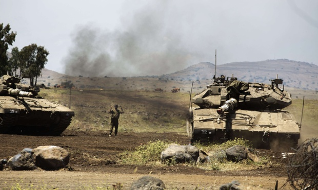 An Israeli soldier directs a Merkava tank in the Israeli annexed Golan Heights near the border with Syria. The head of Israel's armed forces warned Syrian President Bashar al-Assad of 'consequences' if fire continues from Syrian territory against Israeli troops in the occupied Golan Heights.