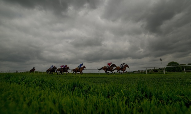 Runners in The Mail Publisher Solutions Handicap Stakes race downhill and into the straight at Lingfield racecourse, England.