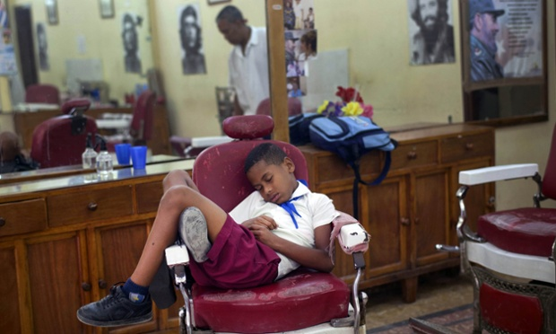 Hurry up Dad. Jose Luis, 7, in his school uniform, falls asleep in a barber's chair, while waiting for his father's work shift to end, in Old Havana, Cuba.