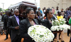 Chinua Achebe's coffin is carried into church for his funeral in Ogidi, south-east Nigeria