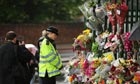 A police officer looks at flowers laid near the scene where Drummer Lee Rigby was killed in Woolwich
