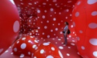 A student stands inside the installation 'Dots Obsessions' by Japanese artist Yayoi Kusama at the exhibition held at the Japanese Foundation centre in Hanoi, Vietnam.