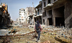 A fighter from the Islamist Syrian rebel group Jabhat al-Nusra walks among damaged houses in Aleppo