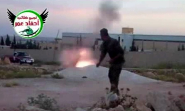 This image from amateur video obtained by a group which calls itself Ugarit News, which AP says is consistent with its reporting, shows a rebel fighter firing a mortar with the help of a drawstring in Aleppo, Syria, on 28 May 2013.