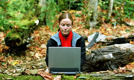A woman using a laptop computer in the forest