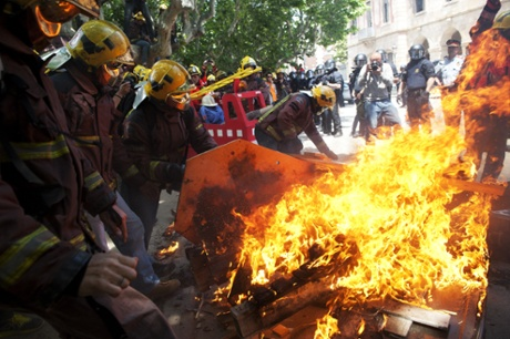 Firemen burned coffins that symbolized the death of the public services due to austerity measures in front of the Catalonia Parliament.