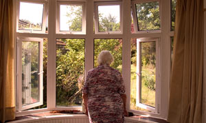 81 year old elderly woman looking out of her front room window, London, UK.